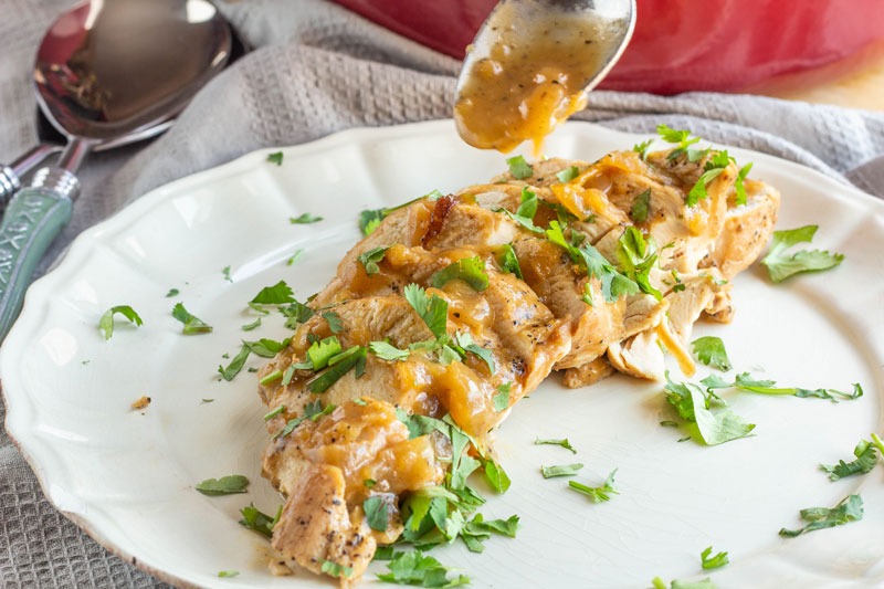 Honey apple braised chicken plated with sauce and cilantro