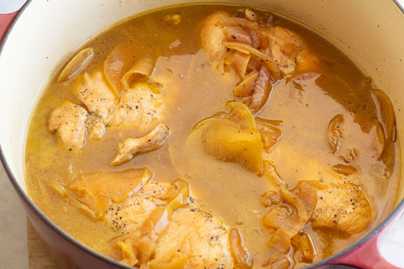 Braised chicken cooking with apples, honey and onions